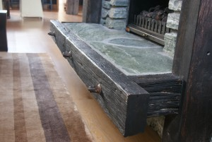 Base of an indoor fireplace with rustic timber and flooring