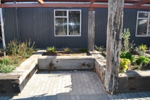 courtyard pace with rustic beams as seats and garden & building behind